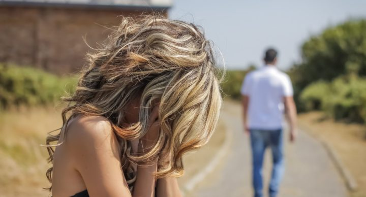 22935891 - unhappy woman in focus crying and angry man leaving on the background after quarrel